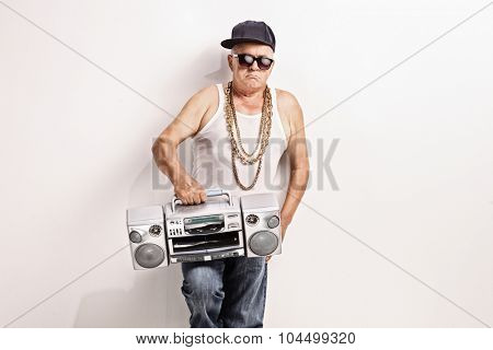 Hardcore senior rapper holding a ghetto blaster and looking at the camera