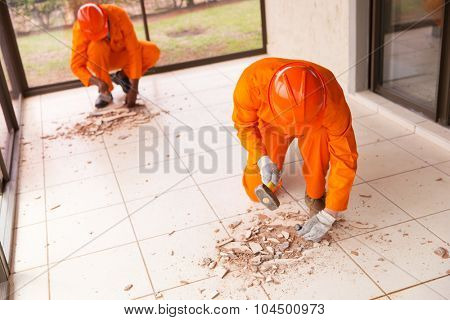 contractors removing old floor tiles using hammer and chisel