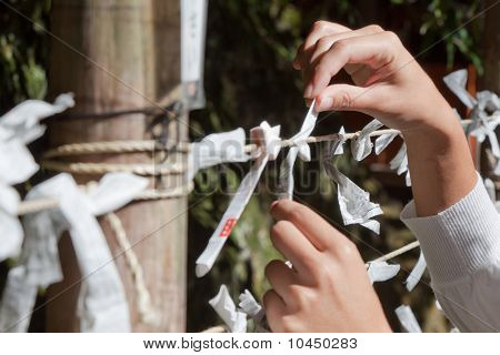 A woman ties her Omikuji fortune paper to a string in a temple in Kyoto Japan poster
