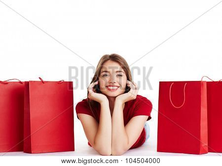 Young shopper looking at camera between red paperbags