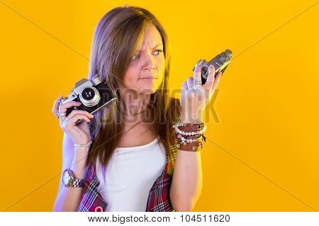Portrait Of Funny Girl With Two Cameras In Their Hands. Stares At The Camera. Isolation On A Yellow