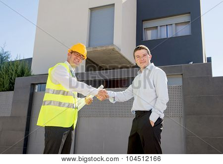 Happy Customer Smiling And Constructor Foreman Worker Shacking Hands As Agreement