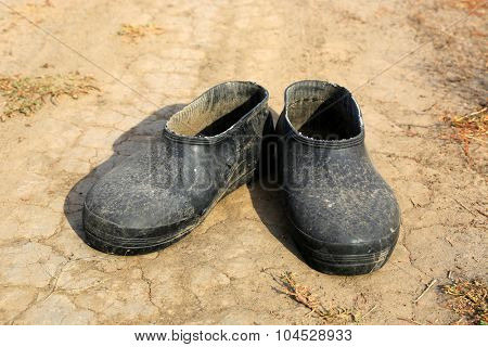 pair of old galoshes on dry soil