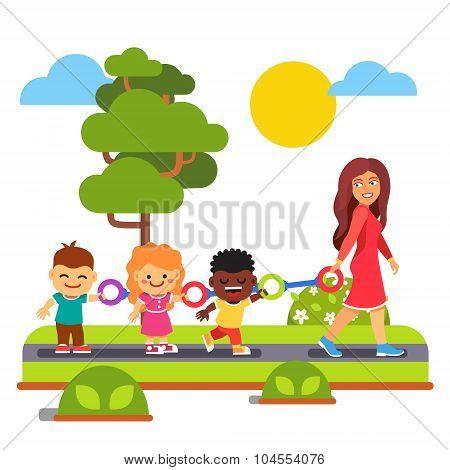 Kindergarten teacher walking with kids outdoors