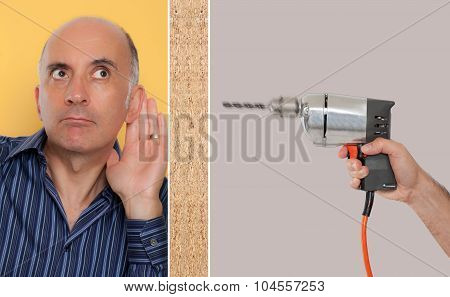 Man leaning against a wall listening to a drill