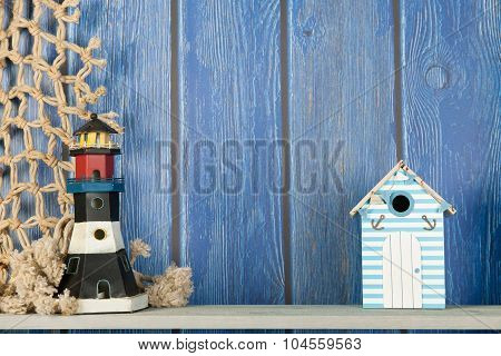 Beach scene with lighthouse and fishing net on blue timbered background