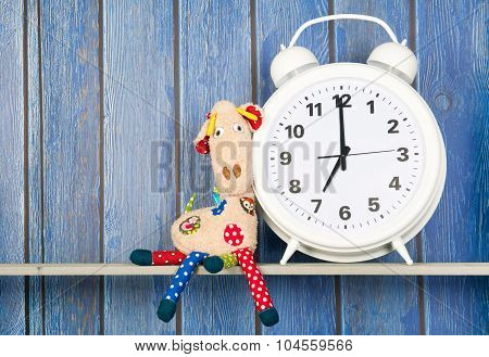 Stuffed animal Giraffe sitting next to alarm clock at seven o'clock isolated over white background