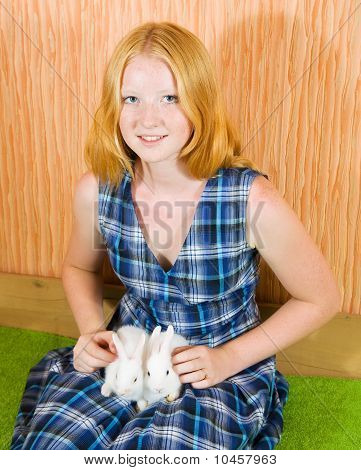 Teen girl with two pet rabbits sitting in home poster