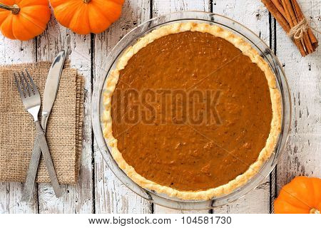 Pumpkin pie downward view on rustic white wood background