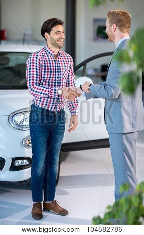 Seller or car salesman and customer in dealership, they shaking hands and seal the purchase of the auto or new car.