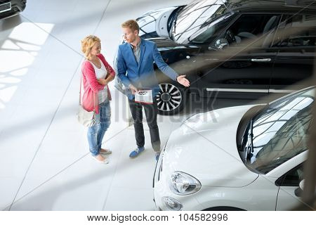 Friendly car dealer showing young women new car in showroom