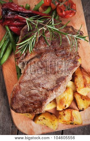 Beef rib-eye steak with roasted potato and vegetables