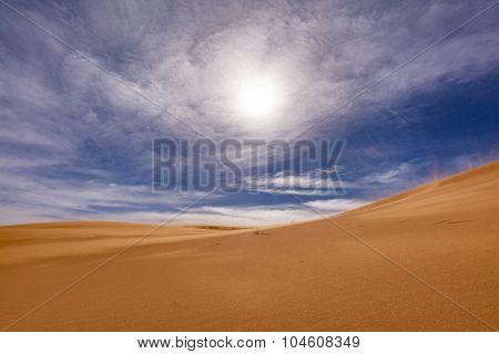 Africa - view of Erg Chebbi Dunes in Morroco- Sahara Desert during strong wind, visible sand particules in sky (not noise) -  backlight effect