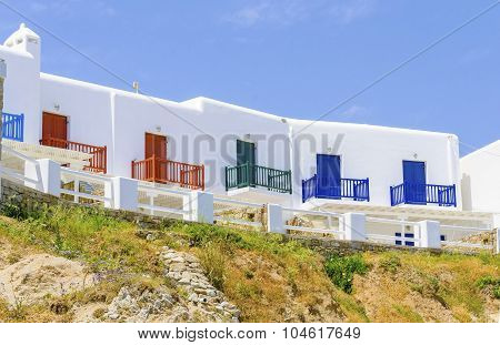 Trational whitewashed cubic beach greek island holiday apartments with blue red and green wooden windows and blacony over a hill facing the sea in Mykonos Greece on a summer day poster