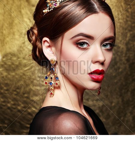 Portrait of sexual stylish girl in a crown on a gold background.Accessorys.