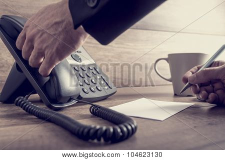 Closeup Of Male Assistant About To Answer A Telephone Call