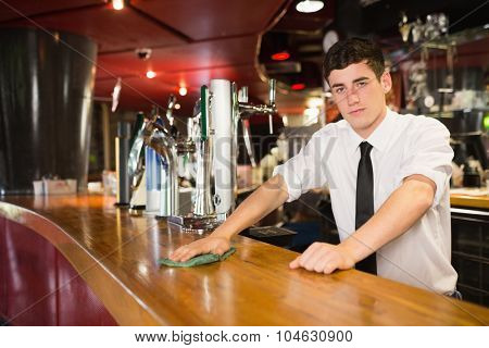 Portrait of confident male bartender cleaning bar counter