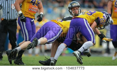 VIENNA, AUSTRIA - JULY 13, 2014: DB Andreas Lunzer (#29 Vikings) and DB Stefan Ruthofer (#9 Vikings) tackle WR Jakub Wolesky (#2 Panthers) during an Austrian football league game.