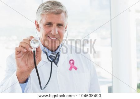 Happy doctor smiling at camera and showing his stethoscope against pink breast cancer awareness ribbon