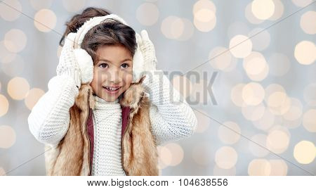 winter, people, christmas, fashion and childhood concept - happy little girl wearing earmuffs and gloves over holidays lights background