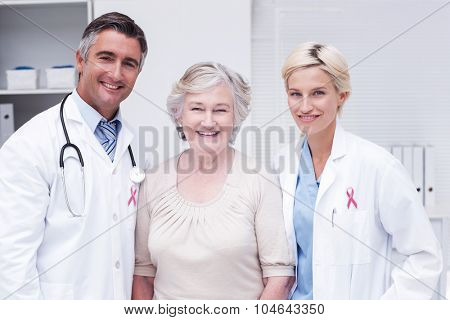 Pink awareness ribbon against doctors and senior patient smiling in clinic