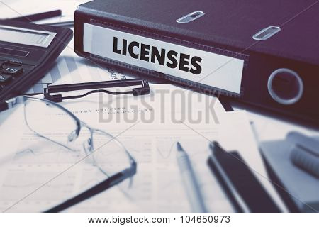 Licenses on Ring Binder. Blured, Toned Image.