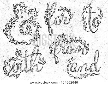 Ink drawn ampersand made of leaves and branches and catchwords in leaves wreaths