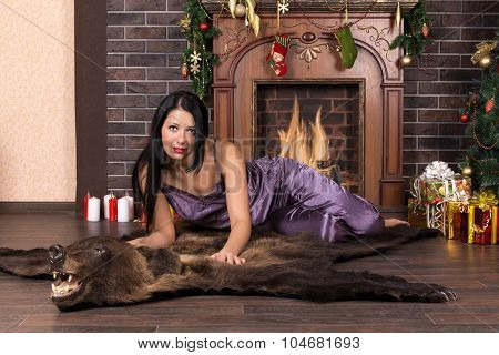 She is at home in front of the fireplace next to Christmas tree