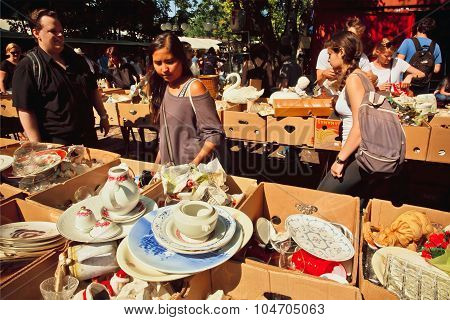 People choose vintage plates and other cookware on flea market