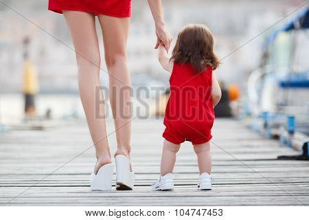Mother and little daughter walking along the waterfront