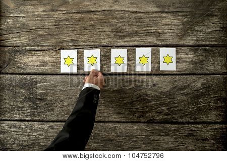 Overhead View Of Male Hand Placing Five Cards With Golden Stars On Them