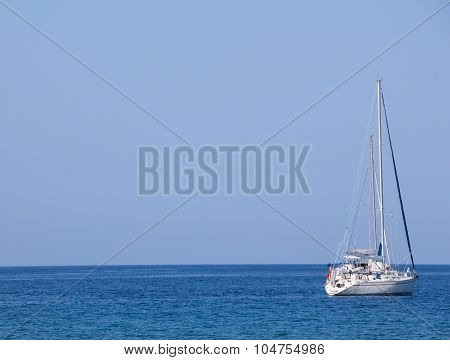 White Yacht With Sails Up On Blue Sea And Sky Horizon