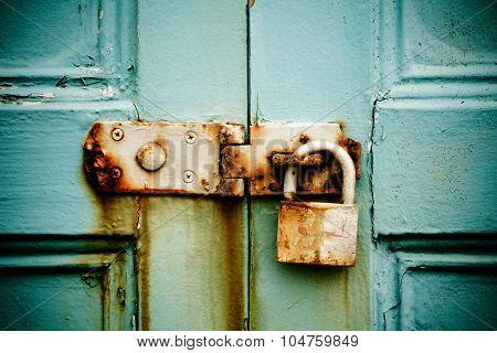 Rusty Padlock On Old Painted Wooden Door