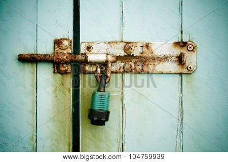 Rusty padlock on painted wooden door to outside shed