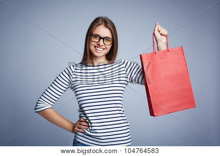 Happy young shopper with red paperbag looking at camera