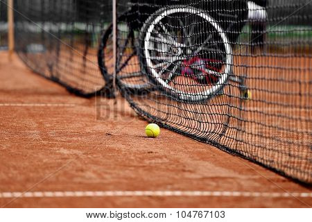 Unfocused wheelchair tennis player is seen behind a tennis net on a clay court poster