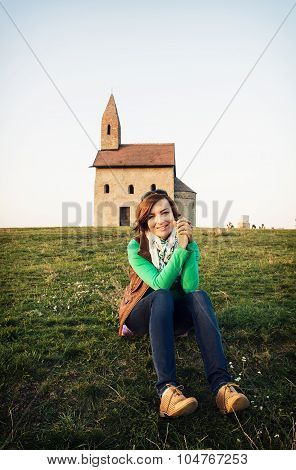 Young Woman Is Sitting In Front Of The Church
