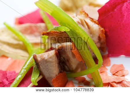 Closeup of a skewer of pork jowls.
