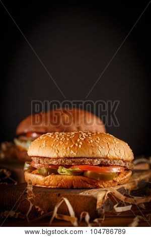 Burger on cutting board on vintage style. Homemade burger or hamburger in dramatic light. Classic burger. Vintage burger or hamburger on old wooden background. Homemade fast food concept. Mouthwatering home made burger. Delicious burger. Rustic burger.
