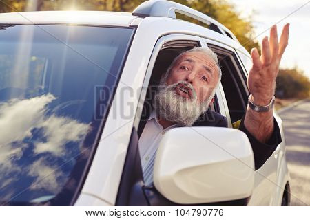 discontented man shouting from the window of his car