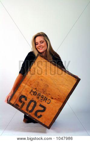 Girl Lifting A Heavy Box