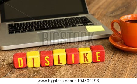 Dislike written on a wooden cube in front of a laptop poster
