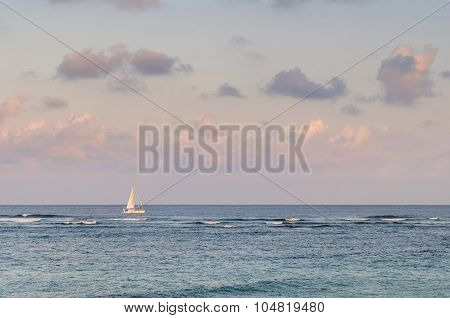 Lone Sailing Boat On The Sea At The Sunset