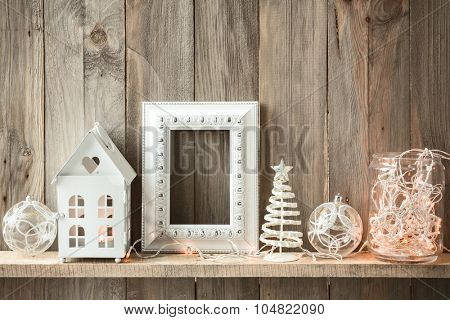Sweet home. White Christmas decor on vintage natural wooden background. Empty photo frame.