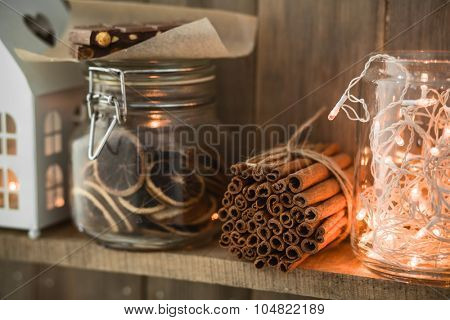 Sweet home. White Christmas decor on vintage natural wooden background. Cinnamon sticks and dried citrus. Cafe shelf. Selective focus.