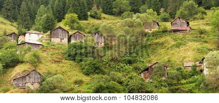 Country outbuildings (sheds) in the coniferous forest on the steep slopes of the Rhodope Mountains in cloudy weather (Rhodopes Bulgaria)