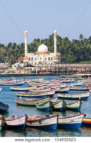 Fishing harbor with colorful boats in the Arabian Sea with the mosque in the background on early sunny morning (Kerala India)