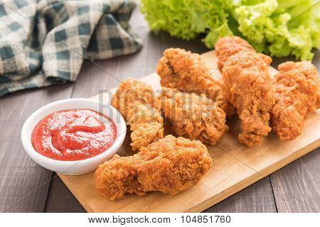 Fried Chicken Drumstick And Vegetables On Wooden Background
