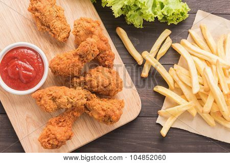 Fried Chicken Drumstick And French Fries On Wooden Background