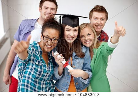 education, graduation, gesture and people concept - group of smiling students in mortarboard with diploma showing thumbs up
